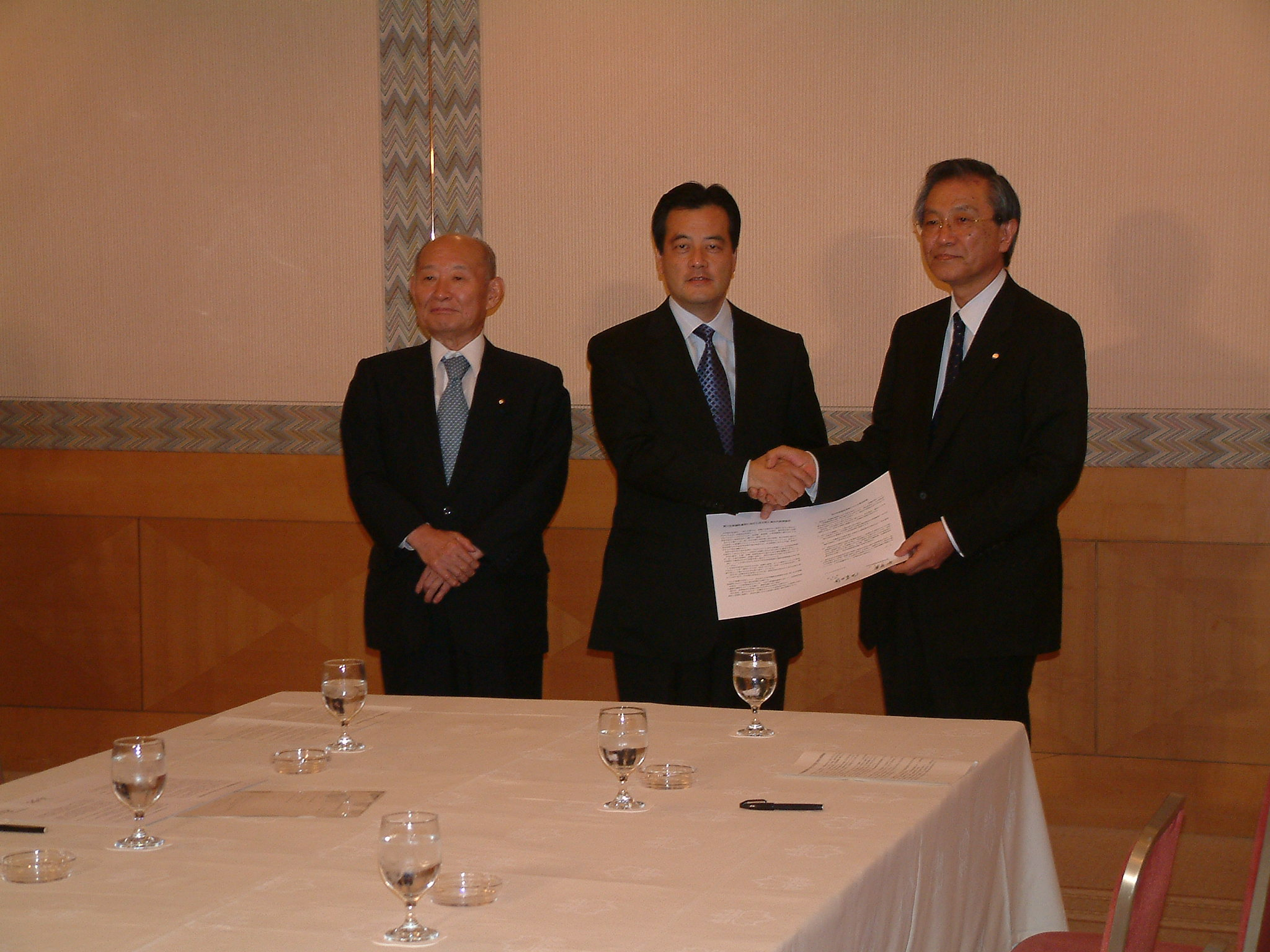 Photo: President Sasamori (right) firmly shaking hands with President Okada of the DPJ.