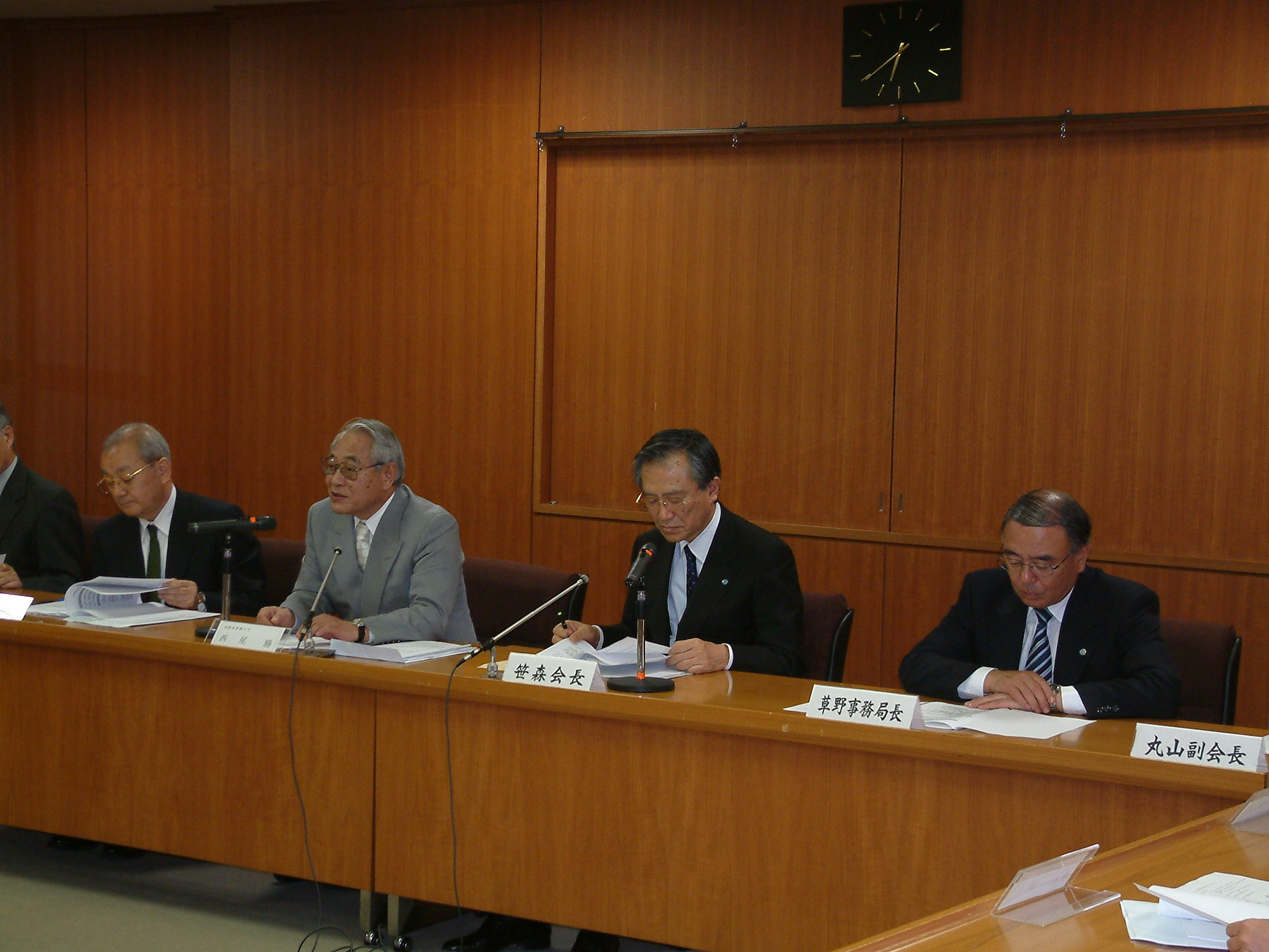 Photo: Chair Nishio (center, right) explains the contents of the report.